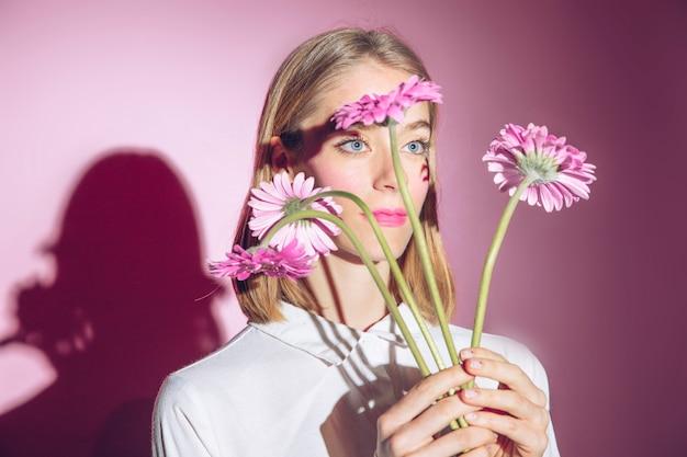Nadenkende vrouw die roze gerberabloemen houdt