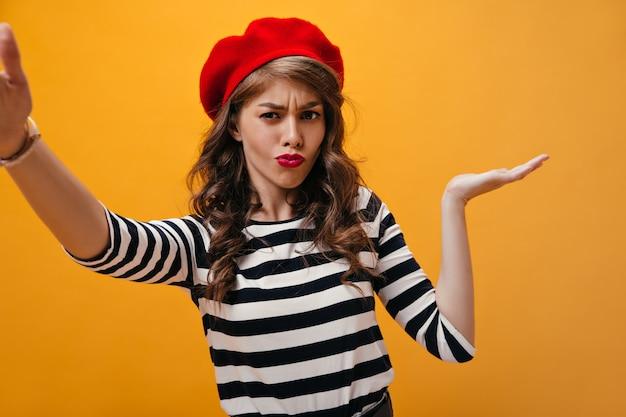 Nadenkende vrouw haalt zijn schouders op en neemt selfie op een oranje achtergrond. stijlvol meisje met krullend haar met rode lippen in moderne kleding poseren.