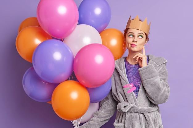 Nadenkende vrouw heeft afbeelding van koningin draagt kroon op hoofd staat nadenkend geconcentreerd boven portemonnees lippen denkt aan komende vakantie viering houdt veelkleurige opgeblazen ballonnen