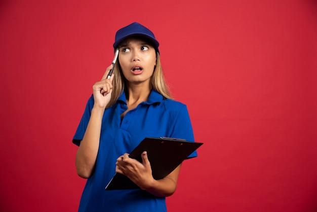Nadenkende vrouw in het blauwe uniform poseren met klembord en potlood.