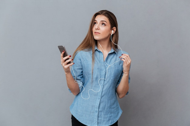 Nadenkende vrouw in overhemd het luisteren muziek op telefoon
