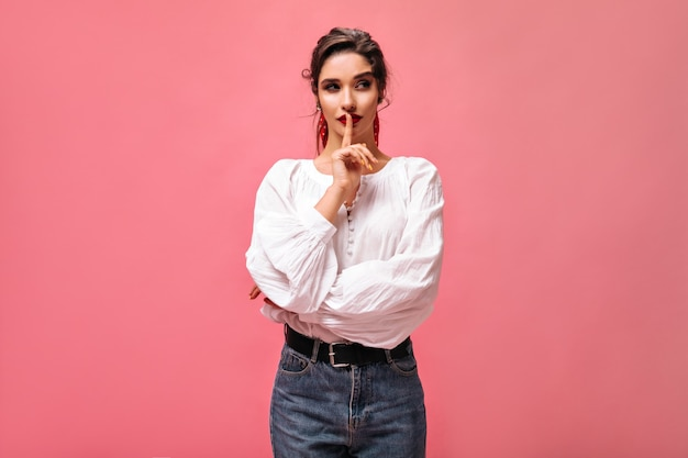 Nadenkende vrouw in witte blouse vormt op roze achtergrond. leuk meisje met rode lippenstift met donker haar in spijkerbroek met brede riem kijkt naar de zijkant.
