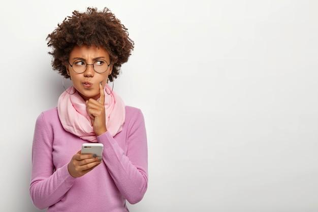 Nadenkende vrouw kijkt bedachtzaam opzij, houdt mobiele telefoon vast, wacht op telefoontje, tuit lippen