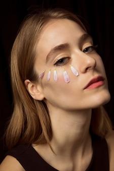 Nadenkende vrouw met bloembloemblaadjes op gezicht