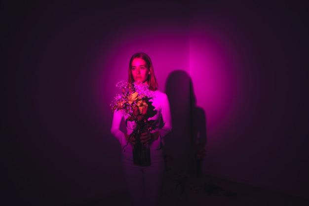 Nadenkende vrouw met bloemen in vaas