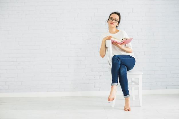 Nadenkende vrouw met boek op stoel