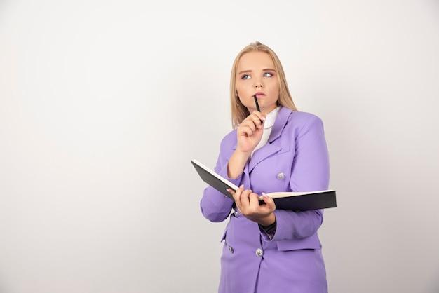 Nadenkende vrouw met geopende tablet en potlood op wit.