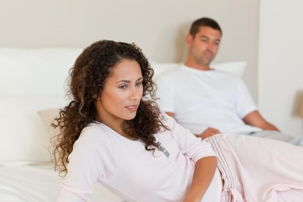 Nadenkende vrouw met haar echtgenoot op het bed