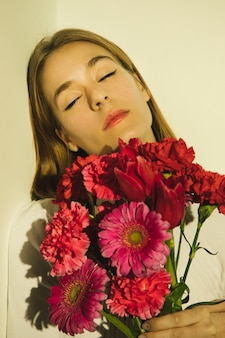 Nadenkende vrouw met helder bloemenboeket