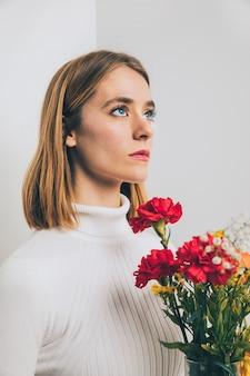 Nadenkende vrouw met heldere bloemen