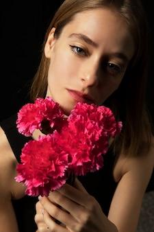 Nadenkende vrouw met roze anjers