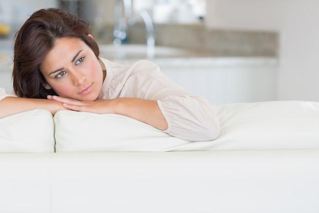 Nadenkende vrouw ontspannen op de bank