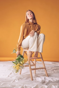 Nadenkende vrouw op ladder met bloemenboeket