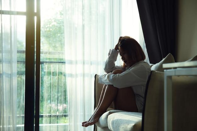 Nadenkende vrouw zittend op vensterbank omhelst knieën, triest depressief tiener tijd alleen doorbrengen.