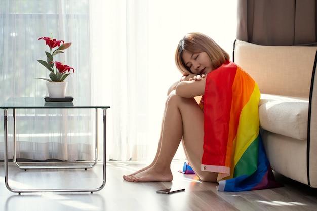 Nadenkende vrouw zittend op vensterbank omhelst knieën