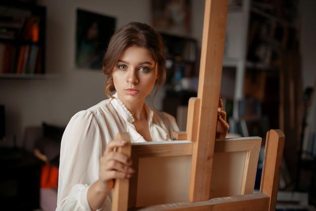 Nadenkende vrouwelijke artiest op de ezel in de studio.