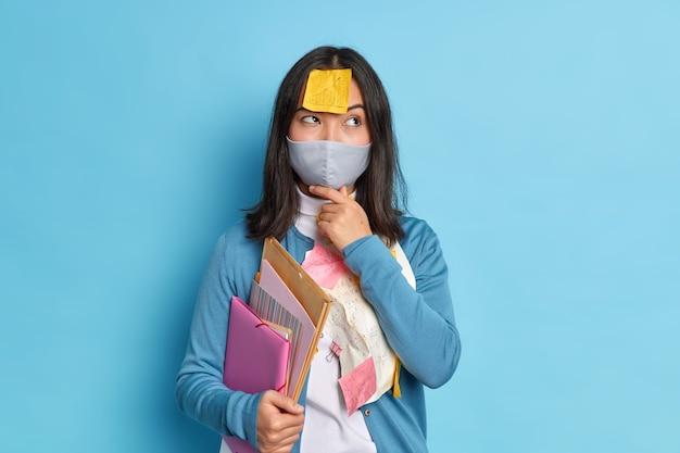 Nadenkende vrouwelijke ondernemer werkt vanuit huis, omdat sociale afstandelijkheid een wegwerpmasker draagt en denkt hoe onderzoekswerk moet worden voorbereid, draagt een casual trui.