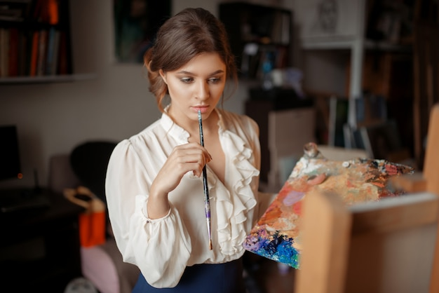 Nadenkende vrouwelijke schilder met kleurenpalet en penseel staande tegen ezel in studio. creatieve penseelkunst, kunstenaarstekeningportret, atelierinterieur op achtergrond