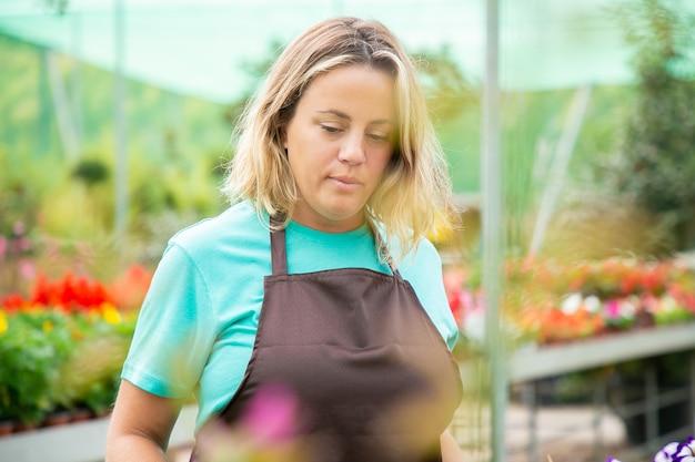Nadenkende vrouwelijke tuinman die neer op iets kijkt