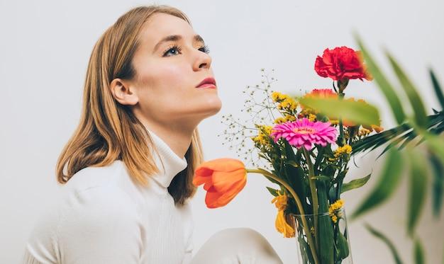 Nadenkende vrouwenzitting met bloemen in vaas