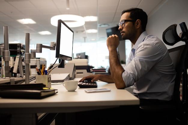 Nadenkende zakenman die aan computer in bureau werkt