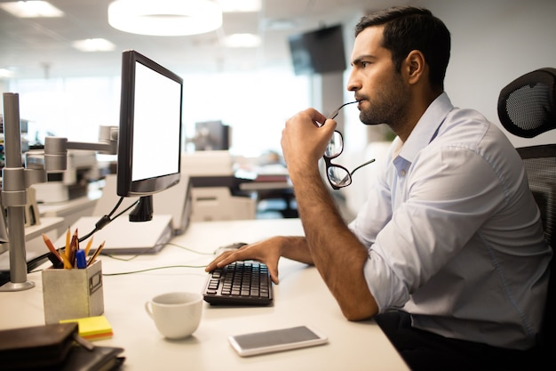 Nadenkende zakenman die computer in bureau met behulp van