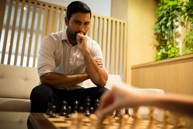 Nadenkende zakenman schaken met vrouwelijke collega