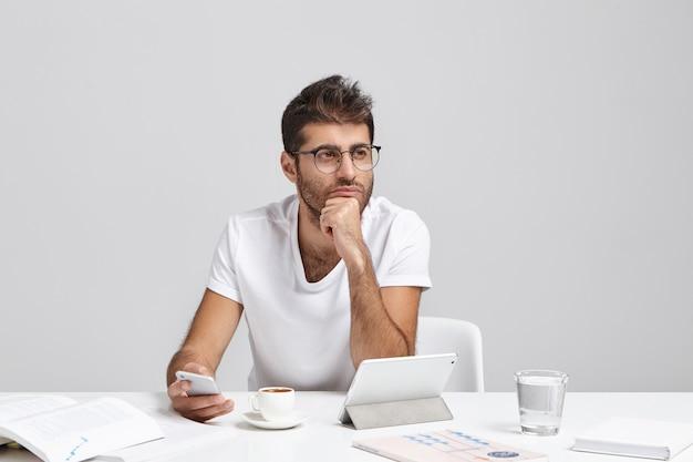 Nadenkende zakenmedewerker probeert zich te concentreren, houdt mobiele telefoon vast terwijl op een belangrijk telefoontje wacht