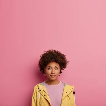 Nadenkende zwarte vrouw met krullend haar kijkt aandachtig naar boven