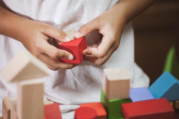 Nadruk op de hand van het kind het spelen met kleurrijke houten blokken in uitstekende kleurentoon