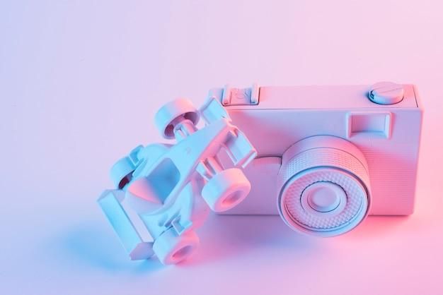 Nadruk van licht over formule één auto over de camera tegen roze achtergrond