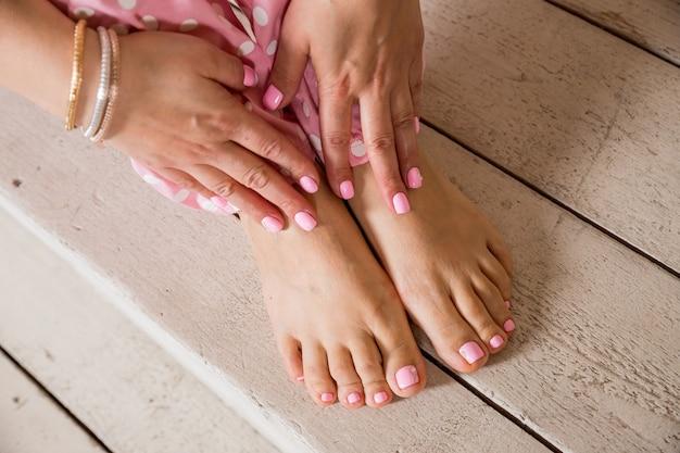 Nagel spa procedure. manicure en pedicure. vrouwelijke handen en voeten op houten vloer. resultaat van de spa-salonprocedure. lichaamsverzorging, spa-behandelingen. nagellak en accessoires. stijlvolle vrouw.