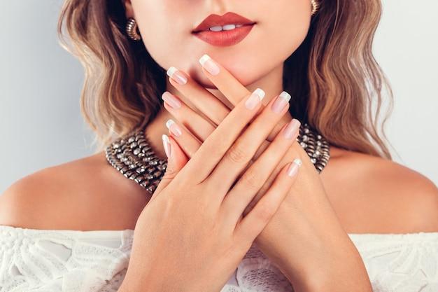 Nagelkunst en ontwerp. mooie vrouw die samenstelling en juwelen draagt en haar franse manicure toont
