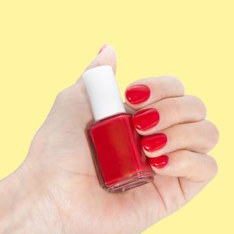 Nagelkunst manicure. fles nagellak. schoonheidssalon. vrouwelijke hand. trendy stijlvolle rode nagels.