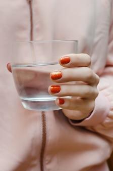 Nagelkunst met glitter. mooie vrouwelijke hand met oranje manicure.
