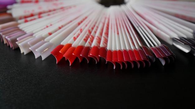 Nagelkunst ontwerp. set valse nagels voor manicure. vernis kleurenpalet voor het schilderen van nagels. kunstnagels op transparante basis. gericht op rode kleur