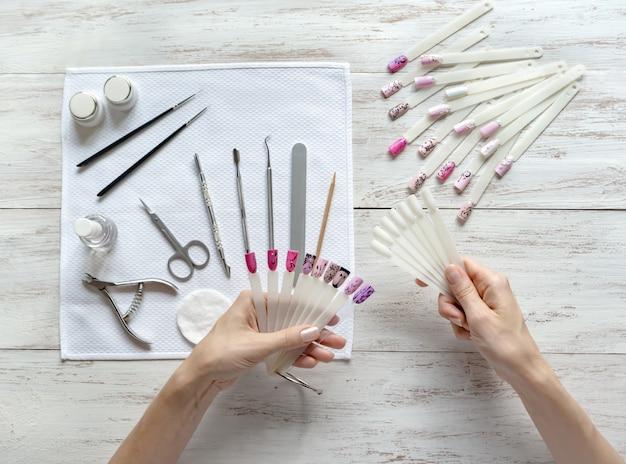 Nagelkunstmonsters in vrouwelijke handen. stel in om nagelontwerp te maken. nagel schoonheid industrie.