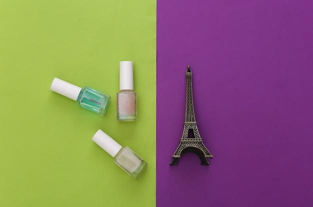 Nagellak en beeldje van de eiffeltoren op een paars groen. schoonheidsconcept