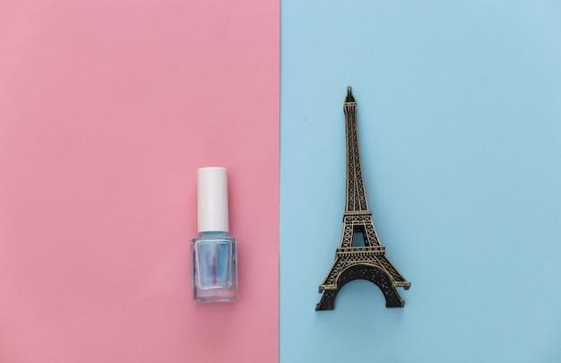 Nagellak en beeldje van de eiffeltoren op roze blauw. schoonheidsconcept