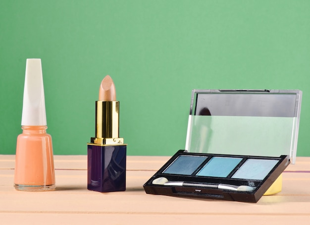 Nagellak, lippenstift, poeder op groene pastel achtergrond