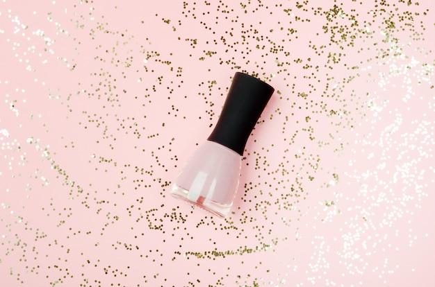 Nagellak roze fles op gouden glitters