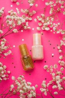 Nagellakken en bloemen op roze tafel
