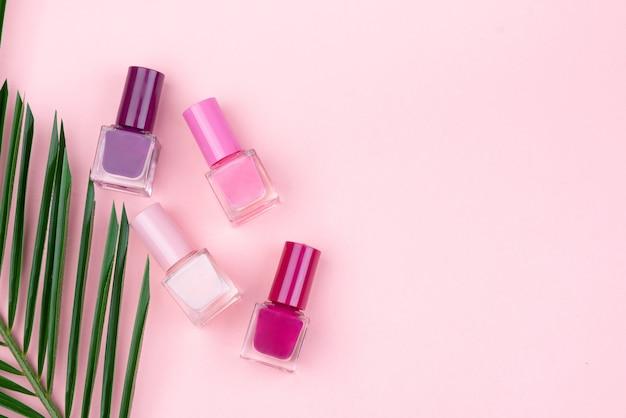 Nagellakken en een palmtak op een roze achtergrond