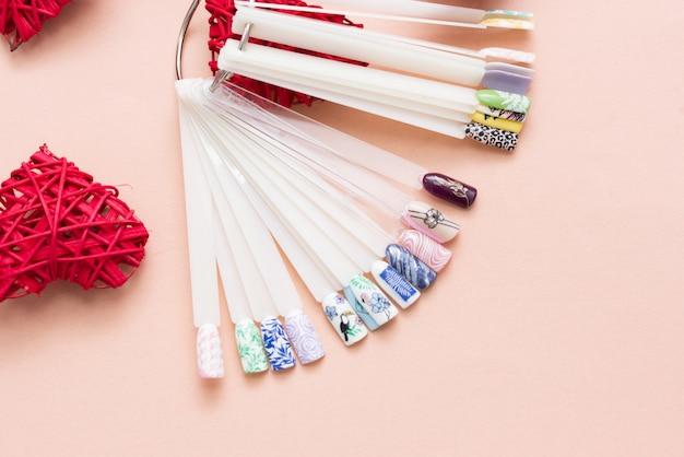 Nagelontwerpen op tips en manicureset op een gekleurde achtergrond.