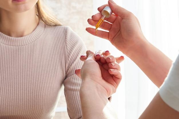 Nagelriemverzorging. vrouwelijke hand olie op nagels toe te passen