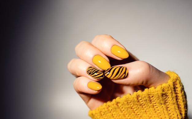 Nagels ontwerp. handen met helder gele manicure op achtergrond. sluit omhoog van vrouwelijke handen. art nagel. tijger manicure