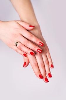 Nagels ontwerp. handen met heldere rode lentemanicure op grijze achtergrond. sluit omhoog van vrouwelijke handen. art nagel.