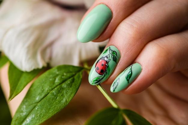 Nagels ontwerp. handen met heldergroene manicure met bloemen. sluit omhoog van vrouwelijke handen. art nagel.