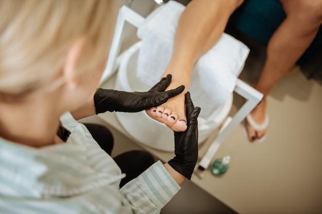 Nagels van voeten. bovenaanzicht van ervaren blondharige pedicure nagels van voeten in het zwart kleuren