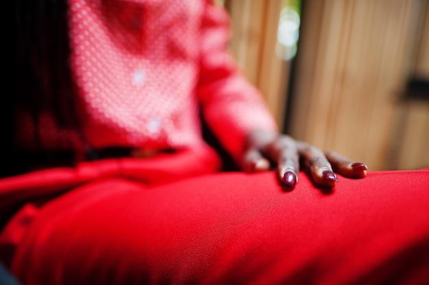 Nagels van zakelijke afro-amerikaanse dame heldere bazige persoon vriendelijke slijtage kantoor rood shirt en broek.
